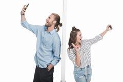 Jeunes couples prenant le selfie avec des smartphones tout en se tenant séparé par le mur Photographie stock libre de droits