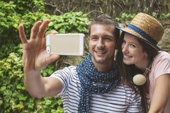 Jeunes couples prenant le selfie avec l'appareil-photo futé de téléphone dedans dehors Image libre de droits