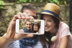 Jeunes couples prenant le selfie avec l'appareil-photo futé de téléphone dedans dehors Photos stock