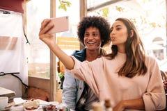 Jeunes couples prenant le selfie avec le téléphone intelligent au café Photo libre de droits