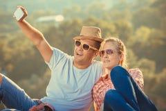 Jeunes couples prenant le selfie d'une colline au-dessus de la ville Photo libre de droits