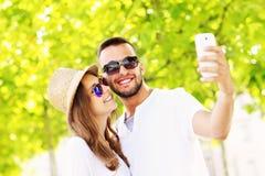 Jeunes couples prenant le selfie en parc Photos libres de droits