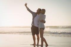 Jeunes couples prenant le selfie sur le rivage à la plage Photos stock