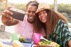 Jeunes couples prenant Selfie pendant le déjeuner dehors Photo stock