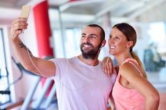 Jeunes couples prenant un sefie dans un gymnase Photo libre de droits