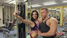 Jeunes couples prenant un sefie dans un gymnase banque de vidéos