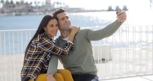 Jeunes couples prenant un selfie au bord de la mer Photographie stock