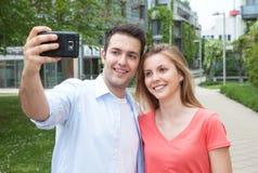 Jeunes couples prenant un selfie avec le téléphone portable Photographie stock libre de droits