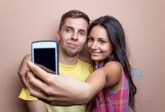 Jeunes couples prenant un selfie avec le téléphone portable Photos stock