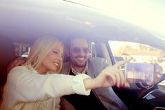 Jeunes couples prenant un selfie dans la voiture Photo stock
