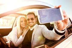 Jeunes couples prenant un selfie dans la voiture Photographie stock libre de droits