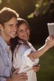 Jeunes couples prenant un selfie en parc Photo libre de droits