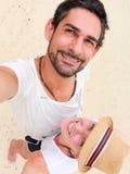 Jeunes couples prenant une photo d'individu près de la mer Images stock