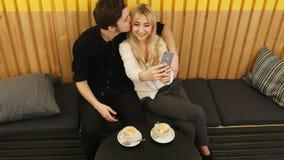 Jeunes couples prenant une photo de lui-même dans un café Photo libre de droits