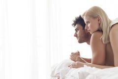 Jeunes couples réfléchis dans le lit Photo stock