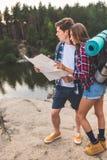 jeunes couples réfléchis des randonneurs avec la carte Photo stock