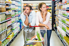 Jeunes couples réfléchis faisant des achats Image stock