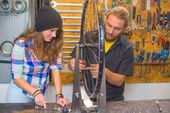 Jeunes couples réparant la bicyclette dans l'atelier images libres de droits