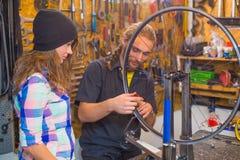 Jeunes couples réparant la bicyclette dans l'atelier photos stock