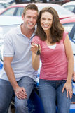 Jeunes couples rassemblant le véhicule neuf Photos libres de droits