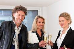Jeunes couples recherchant les immeubles avec l'agent immobilier Images libres de droits