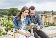 Jeunes couples regardant dans une carte Photographie stock libre de droits