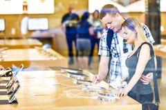 Jeunes couples regardant de derniers comprimés montrés Photo stock