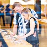 Jeunes couples regardant de derniers comprimés montrés Image stock