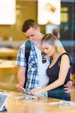 Jeunes couples regardant de derniers comprimés montrés Images stock