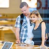 Jeunes couples regardant de derniers comprimés montrés Photographie stock libre de droits