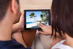 Jeunes couples regardant des photos sur le comprimé numérique ensemble Photos stock