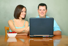 Jeunes couples regardant l'ordinateur portatif sur la table de cuisine Photo stock