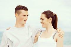 Jeunes couples regardant l'un l'autre tout en se tenant sur la plage Photographie stock libre de droits
