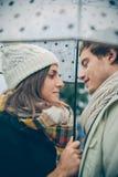 Jeunes couples regardant l'un l'autre sous le parapluie Images stock