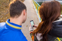 Jeunes couples regardant la carte au téléphone portable Image stock