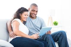 Jeunes couples regardant la tablette Photographie stock libre de droits