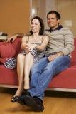 Jeunes couples regardant la TV dans la chambre d'hôtel Photo stock
