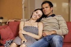 Jeunes couples regardant la TV dans la chambre d'hôtel Image libre de droits