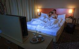 Jeunes couples regardant la TV dans la chambre d'hôtel la nuit Image stock