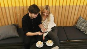 Jeunes couples regardant le comprimé et buvant du café Photos stock