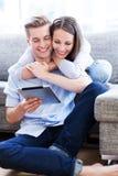Jeunes couples regardant le comprimé numérique Images stock