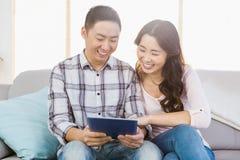 Jeunes couples regardant le comprimé numérique Photos libres de droits