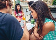 Jeunes couples regardant le smartphone dehors en été Photo stock