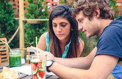 Jeunes couples regardant le smartphone dehors en été Photographie stock libre de droits