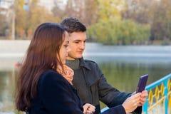 Jeunes couples regardant le téléphone portable ensemble Photographie stock libre de droits