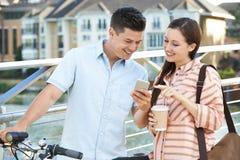 Jeunes couples regardant le téléphone sur le chemin de travailler dans l'environnement urbain Photographie stock libre de droits