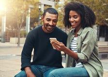 Jeunes couples regardant le t?l?phone portable image libre de droits