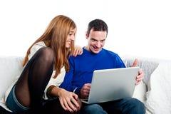 Jeunes couples regardant quelque chose sur un ordinateur Images stock