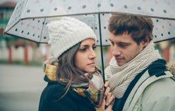 Jeunes couples regardant sous le parapluie dans un jour pluvieux Images stock