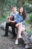 Jeunes couples reposant sur un identifiez-vous la forêt et jouant la guitare, nature d'été, sentiments romantiques image stock